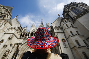A man wears a hat printed with Union Flags outside the Royal Courts of Justice in London
