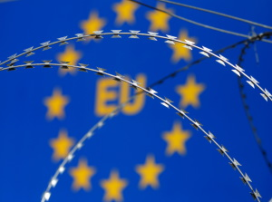 Razor wire is seen in front of an EU sign during a protest against barbed wire fences along the border crossing between Slovenia and Croatia in Brezovica pri Gradinu