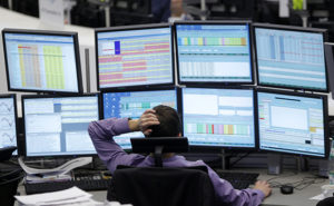 A trader watches screens at his desk at the Frankfurt stock exchange